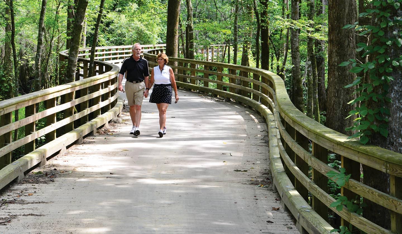 Couple walking across a bridge through Carolina Colours private residential retirement community trails