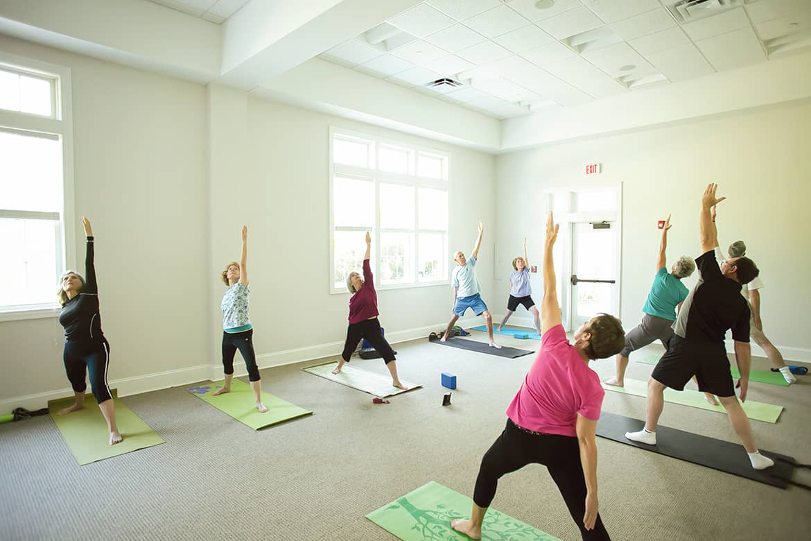Carolina Colours residents participating in private community yoga classes on-site at pavilion clubhouse