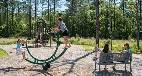 Parents sitting and playing with young children at Carolina Colours residential community playground on a summer day