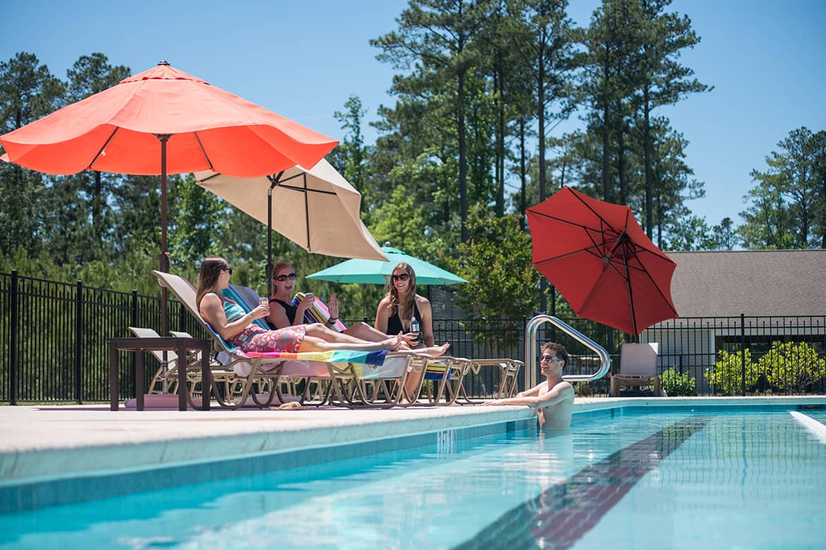 Carolina Colours residents talking and swimming poolside at the private community pool